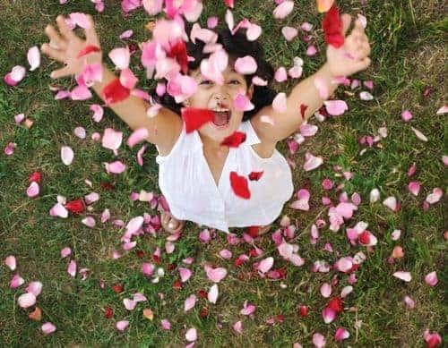 Enfant joyeuse avec des pétales de roses